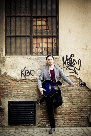 Junge, attraktive Straßenkünstler mit seiner Gitarre. Lizenzfreie Bilder