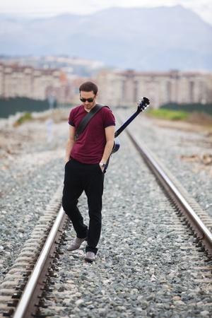 Junger männlicher Musiker walking mit seiner akustischen Gitarre.