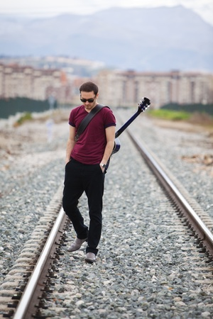 alone man: Young male musician walking with his acustic guitar.