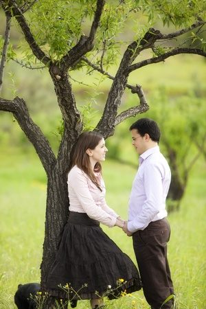 heart under: Young lovely couple staring each other in nature.