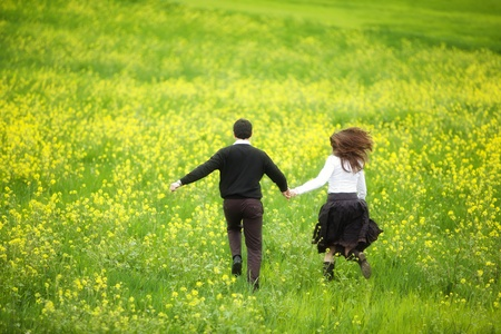 spring break: Young couple running together on a green and yellow field. Stock Photo