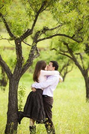heart under: Young lovely couple kissing under nature.