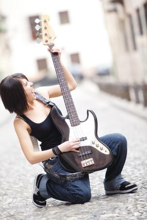 Joyful young woman playing a guitar at the street Stock Photo - 9017268