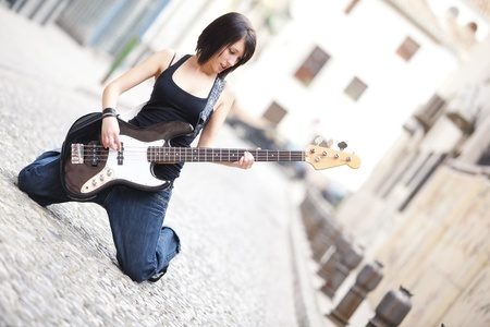 Joyful young woman playing a guitar on her knees photo