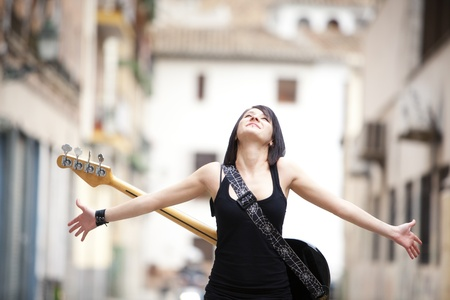Young beautiful guitarist in urban background. photo