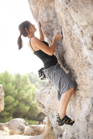 Young beautiful woman climbing a rock wall. photo