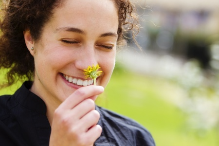 Young beautiful curly woman smelling and smiling. photo