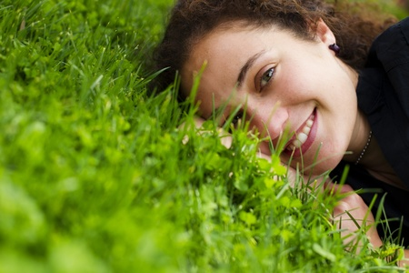Young happy girl smiling at camera over the grass Standard-Bild