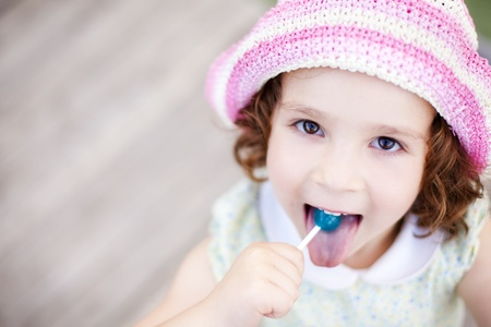 girl licking: Little kid enjoying a lollypop while staring at camera from below