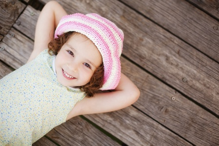 women children: Pretty child lying on wooden surface.