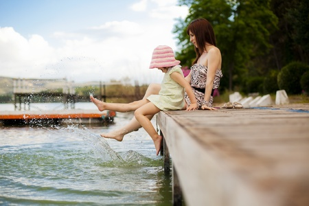 copyspace: Young mother and her daughter splashing in the lake
