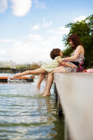 Jeune maman et sa fille éclaboussures dans le lac