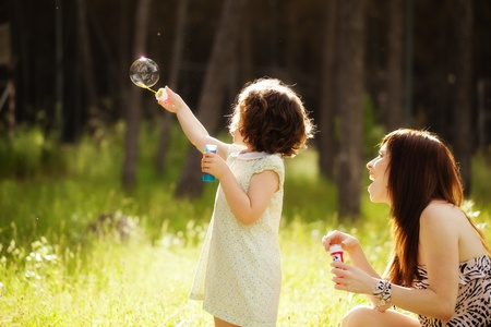 Young mother and her child playing with soap bubbles Фото со стока