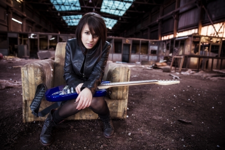 Young beautiful performer posing with her electric guitar. Stock Photo - 17825313