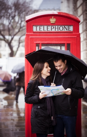 couple in rain: Sweet honeymoon couple consulting map in London Stock Photo