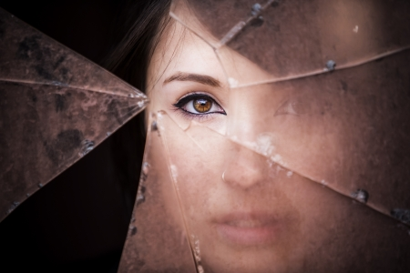 bad condition: Woman looking through dirty broken glass Stock Photo