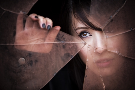 look through window: Woman looking through dirty broken glass Stock Photo