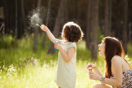 Jeune maman et son enfant jouant avec des bulles de savon Banque d'images