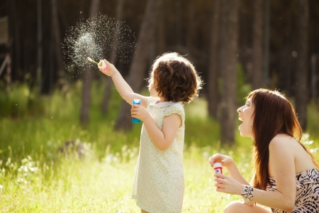 soap bubbles: Young mother and her child playing with soap bubbles Stock Photo