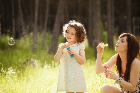 Young mother and her child playing with soap bubbles Stock Photo