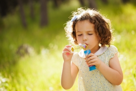 Portrait of funny lovely little girl making soap bubbles. Free space for your own bubbles. photo