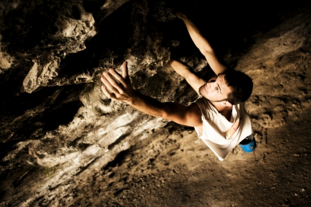 free climbing: Young make climber doing a rock wall on a cave.