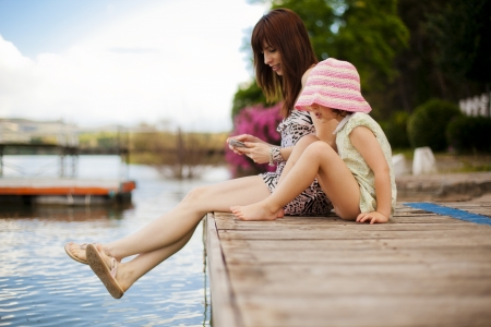 Young mother and her daughter sitting on a pier photo