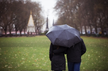couple in rain: Young couple taking a walk in the park on a rainy day