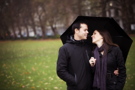 Young sweet couple sharing umbrella and smiling each other photo