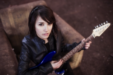 Young beautiful female performer posing with her electric guitar. photo