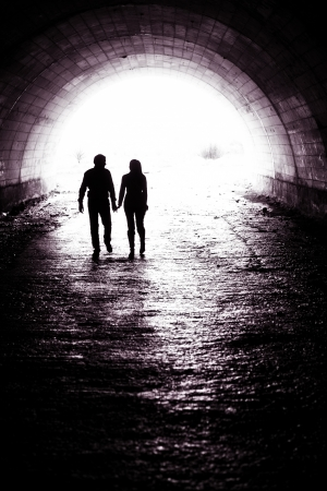 tunnel view: Silhouette of a couple holding hands and walking together in darkness