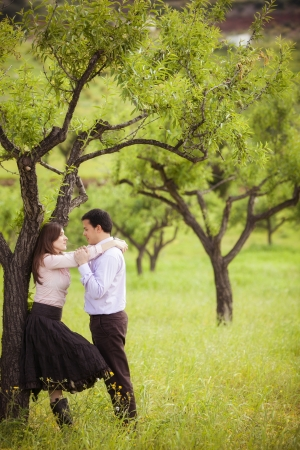under tree: Young lovely couple staring each other in nature.