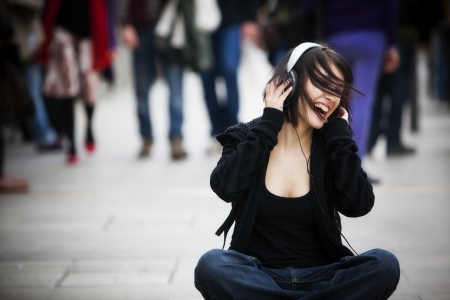 woman listening to music: Young beautiful urban girl singing among the crowd.