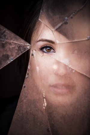 spies: Woman looking through dirty broken glass Stock Photo