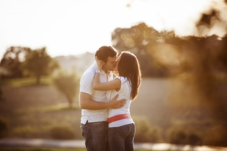 Young beautiful romantic couple in backlit composition photo
