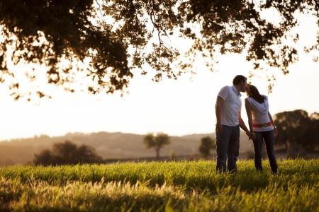 Young kissing couple on idyllic background photo
