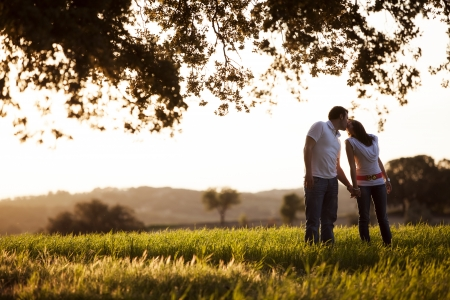 Young kissing couple on idyllic background