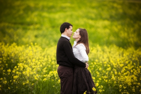Young loving couple showing their love on a green field
