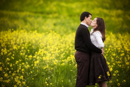 Young loving couple kissing on a green field