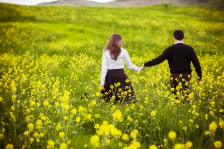 Young coupletaking a walk on beautiful flower field.