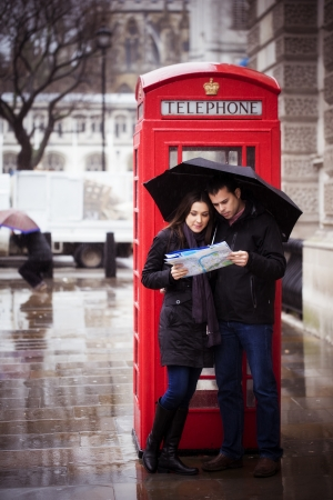 Sweet honeymoon couple consulting map in London photo