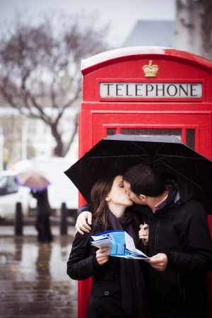 Sweet honeymoon couple kissing instead of consulting map in London photo
