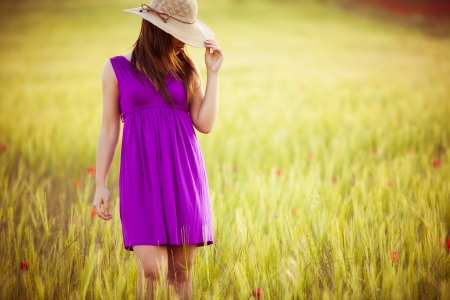 Young girl on field hiding behind her hat. photo
