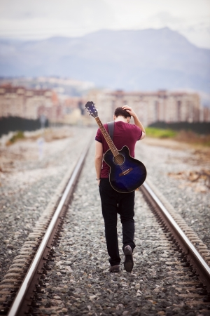railways: Young male musician walking with his acustic guitar.