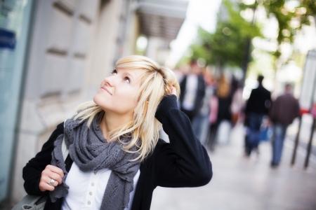 Joven hermosa chica urbana mirando lo que la rodea.