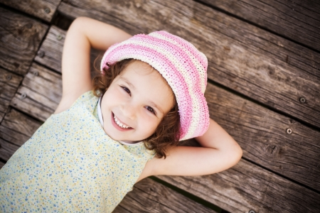 cute little girl smiling: Pretty child lying on wooden surface.