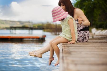 belles jambes: Jeune maman et sa fille éclaboussures dans le lac