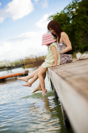 little girl barefoot: Young mother and her daughter splashing in the lake