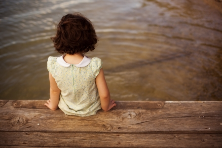 little girl beach: Lone little girl sitting on pier