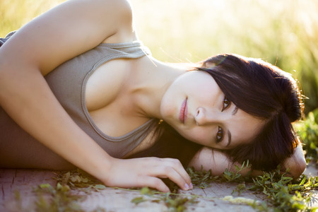 Young beautiful girl laying in nature, under the sun. photo